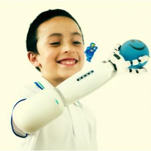 Enfant équipé d'un  IKO Creative Prosthetic System, jouant avec un petit personnage Lego.