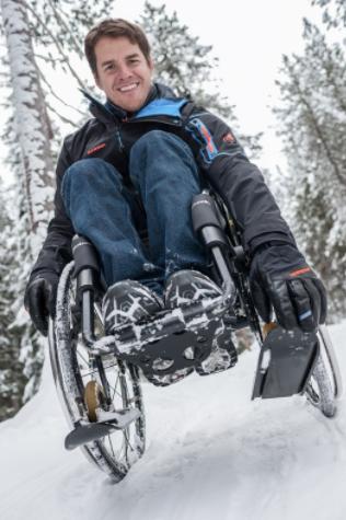 Diapo 4 : Personne utilisant un fauteuil roulant équipé de mini-skis dans la neige.