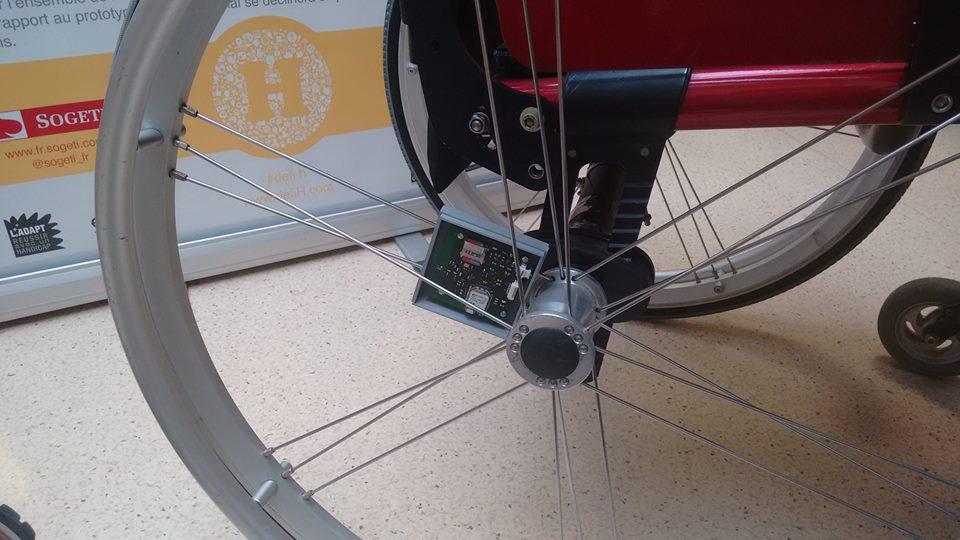 Diapo 3 : Gros plan sur un capteur Handi'perf, situé sur la roue d'un fauteuil roulant.