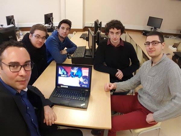Diapo 4 : Cinq personnes assises autour d'une table, avec des ordinateurs, regardant la caméra.