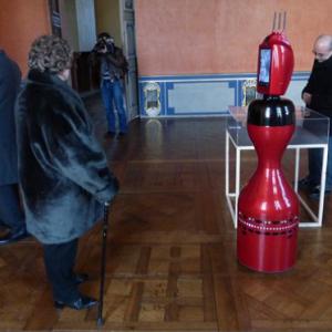Robot Norio dans une salle d'un bâtiment ancien, face à des visiteurs.