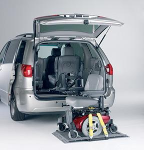 Diapo 4 : Voiture de dos, coffre ouvert. Un fauteuil roulant est posé sur une plateforme devant le coffre.