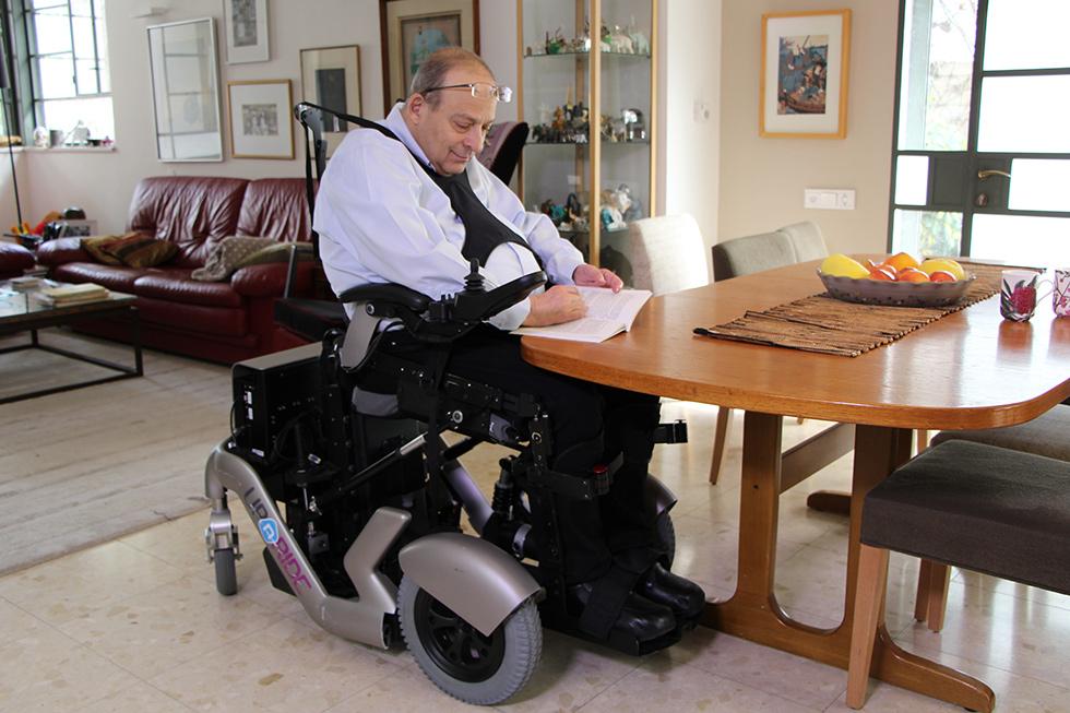 Diapo 2 : Personne se déplaçant dans un fauteuil UPnRIDE, écrivant à une table en position assise.