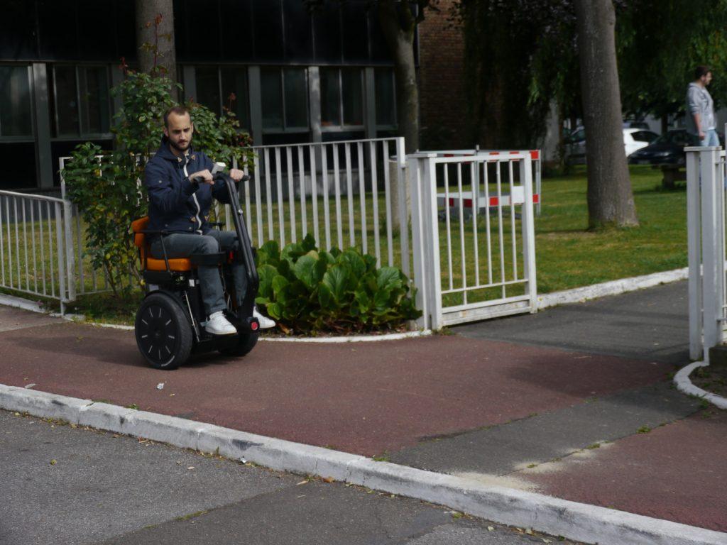 Diapo 5 : Personne se déplaçant dans la rue dans un fauteuil Gyrolift, en position assise.