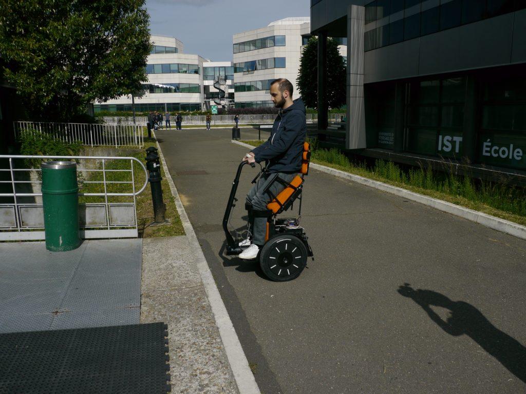 Diapo 2 : Personne se déplaçant dans la rue dans un fauteuil Gyrolift, en position debout.