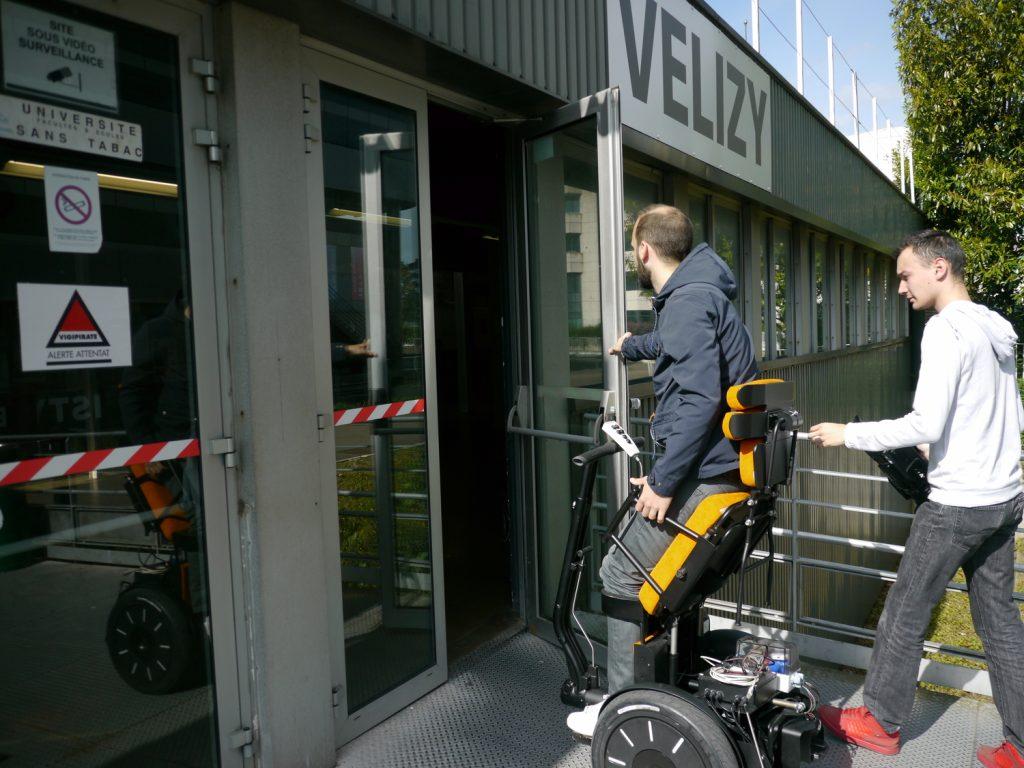 Diapo 3 : Personne se déplaçant  dans un fauteuil Gyrolift en position debout entrant dans un bâtiment.