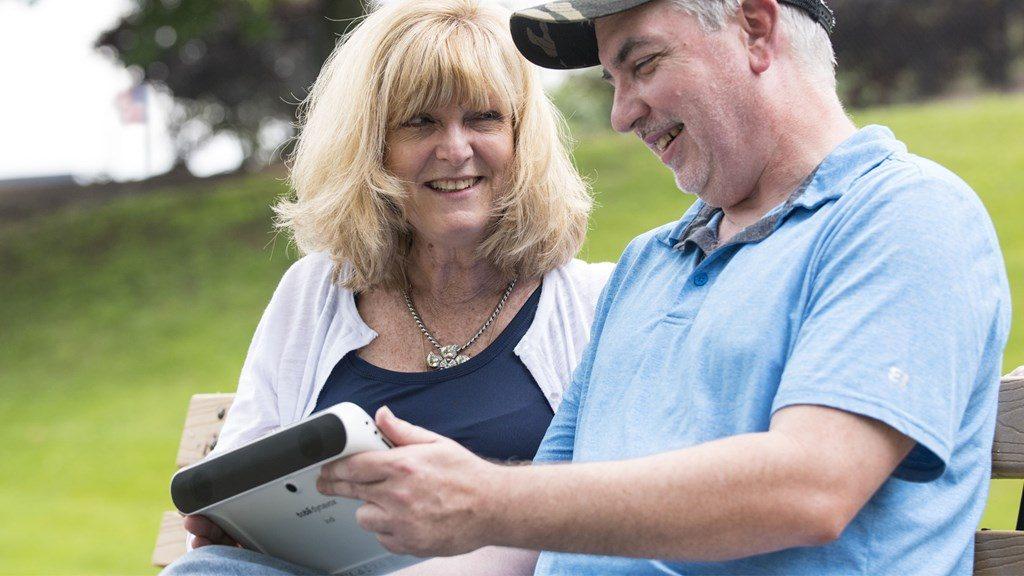 Diapo 2 : Deux personnes souriantes en extérieur, tenant dans leurs mains une tablette indi.