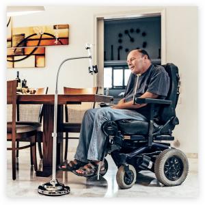 Personne en fauteuil roulant face à un présentoir sur lequel est attaché un Sesame Phone.
