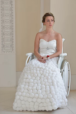 Diapo 4 : Femme en fauteuil roulant, portant une robe de mariée.