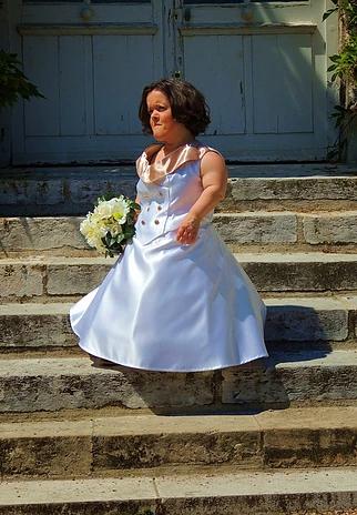 Diapo 2 : Femme de petite taille, portant une robe de mariée et tenant un bouquet de fleurs dans la main.