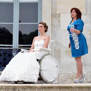 Femme en fauteuil roulant, portant une robe de mariée, à coté d'une autre femme, debout.