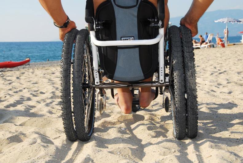 Diapo 1 : Fauteuil roulant à roues larges, roulant sur du sable.