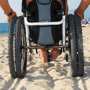 Fauteuil roulant à roues larges, roulant sur du sable.