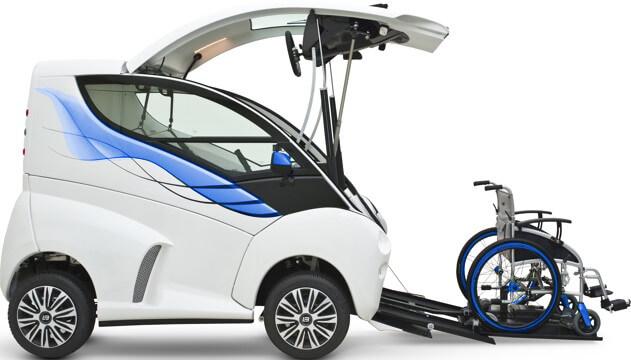 Diapo 5 : Voiture Elbee grise  et bleue de profil, ouverte et prête à accueillir un conducteur en fauteuil roulant. Des rampes pour fauteuil on étés déployées.