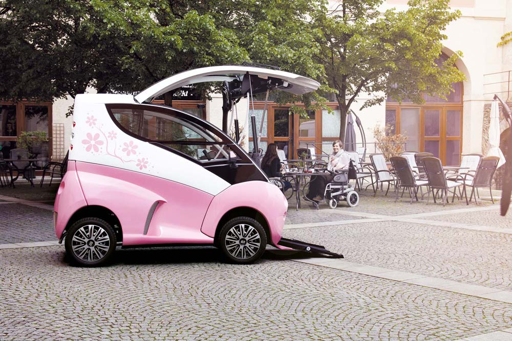 Diapo 3 : Voiture Elbee rose de profil, ouverte et prête à accueillir un conducteur en fauteuil roulant. Des rampes pour fauteuil on étés déployées. Elle est situé à proximité de la terrasse d'un café.