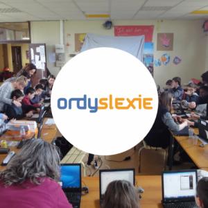 Enfants étudiant en classe sur des ordinateurs, le logo Ordylexie apparaît au centre.