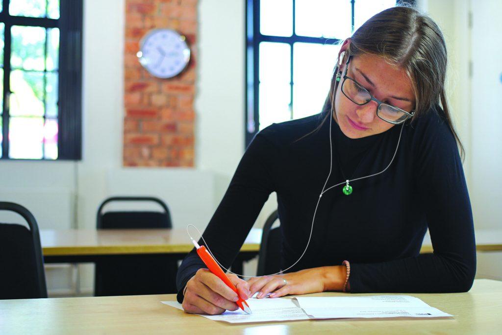 Diapo 2 : Étudiant utilisant un Exam Reader pour lire un document dans une salle de classe.