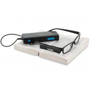 Appareil et caméra MyEye, équipés sur une paire de lunettes, posée sur un livre ouvert.