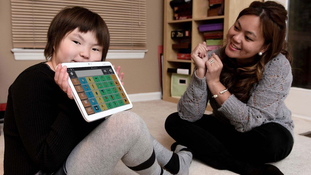 Diapo 3 : Gauche de l'image: un enfant tient une tablette Indi, affichant  le clavier de pictogrammes de l'application Core First. Droite de l'image: un adulte l'encourage.