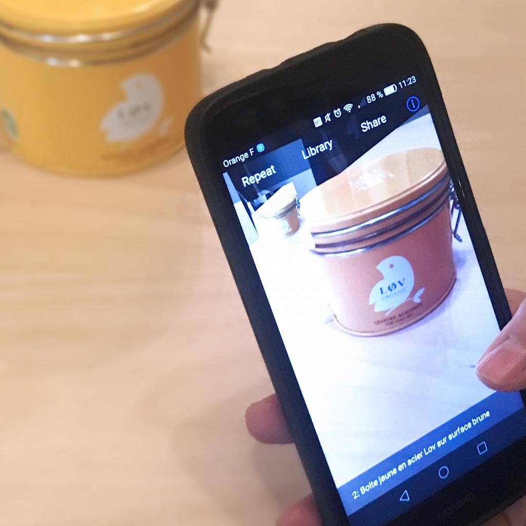 Diapo 2 : Personne utilisant l'application TapTapSee sur son smartphone pour identifier un objet posé sur une table. L'application indique 'Boite jaune en acier Lov sur surface brune'.