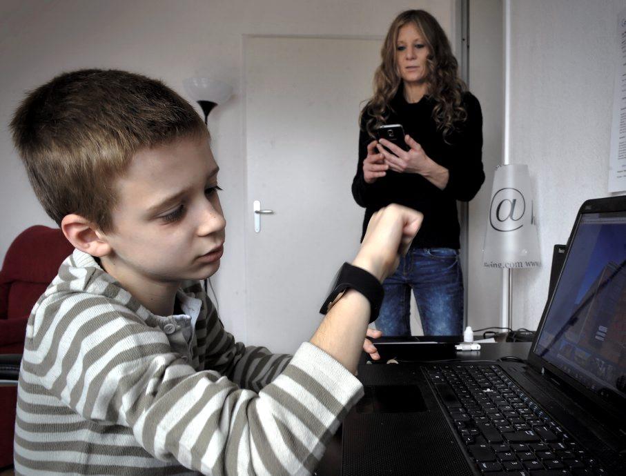 Diapo 3 : Enfant regardant l'application Watchelp sur sa montre connectée, pendant qu'un adulte la regarde sur un smartphone.