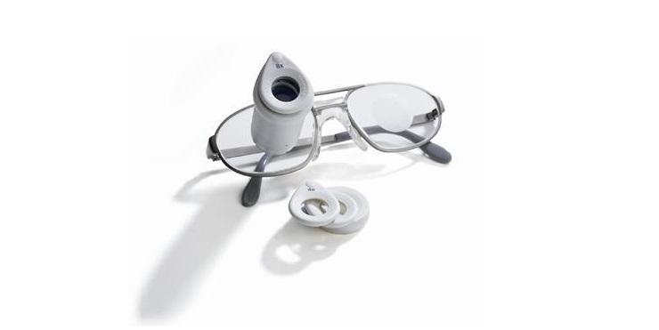 Diapo 3 : Lunettes ZEISS G2 BIOPTICS posées sur une surface blanche. Des lentilles de rechange pour la loupe intégrée sont posées sur le coté.