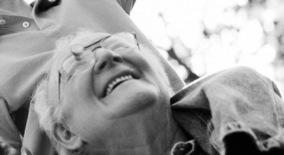 Diapo 2 : Personne souriante portant des lunettes ZEISS G2 BIOPTICS en extérieur.