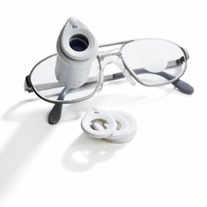 Lunettes ZEISS G2 BIOPTICS posées sur une surface blanche. Des lentilles de rechange pour la loupe intégrée sont posées sur le coté.