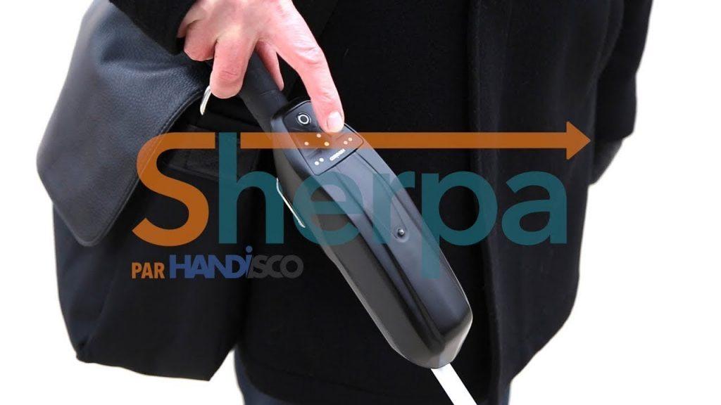 Diapo 4 : Gros plan sur une personne appuyant sur un bouton du boitier Sherpa installé sur sa canne blanche, le logo 'Sharpa par Handisco' est visible en transparence.