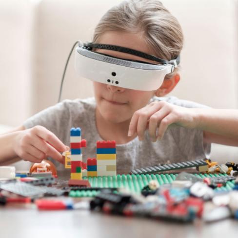 Diapo 4 : Enfant jouant, en portant des lunettes eSight.