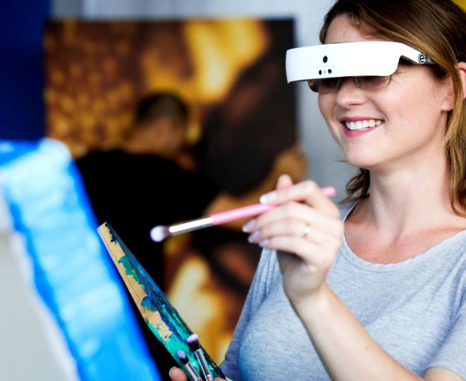 Diapo 3 : Personne peignant en utilisant des lunettes eSight.