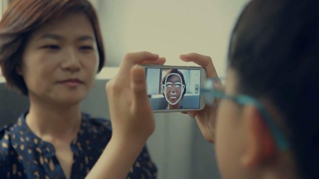 Diapo 2 : Personne utilisant la fonction de reconnaissance faciale de look at me sur une autre personne