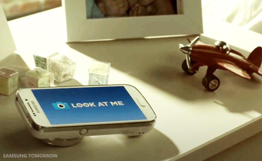 Diapo 3 : Téléphone affichant le logo de look at me, posé sur une table avec model d'avion et cadre photo.