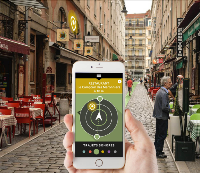 Diapo 3 : Personne se rendant au restaurant ' Le comptoir des marronniers' grâce à l'application Wizigo sur son smartphone. Fond de l'image: rue piétonne.