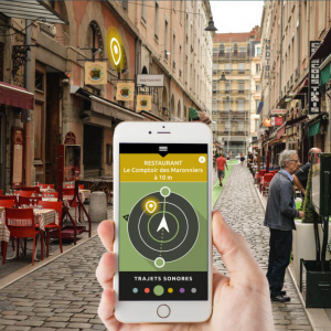 Personne se rendant au restaurant » Le comptoir des marronniers» grâce à l'application Wizigo sur son smartphone. Fond de l'image: rue piétonne.