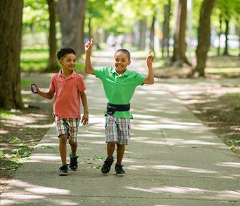 Diapo 3 : Deux enfants marchant dans un parc, l'un d'eux porte une ceinture Navibelt.
