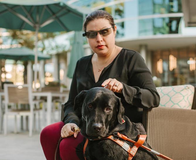 Diapo 3 : Personne équipée du dispositif Aira (lunettes et oreillettes) , assise, avec son chien guide d'aveugle.