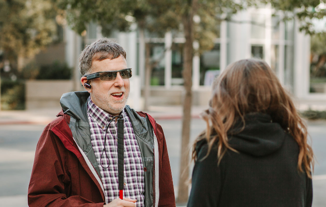 Diapo 2 : Personne équipée du dispositif Aira (lunettes et oreillettes) , discutant avec une autre personne.