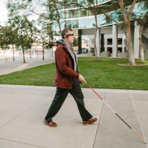 Personne équipée du dispositif Aira (lunettes et oreillettes) , marchant dans la rue à l'aide d'une canne blanche.