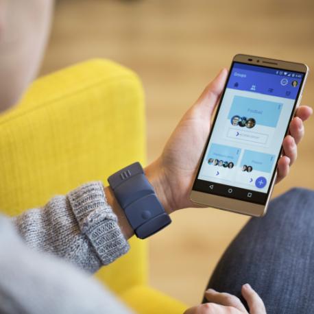 Diapo 3 : Personne assise, portant un bracelet Unitact au poignet gauche et utilisant un smartphone de la main gauche.