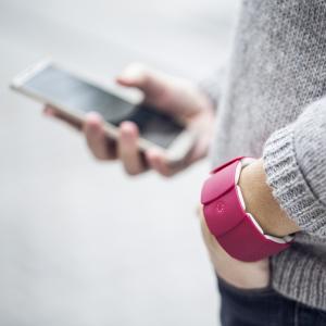 Personne portant un bracelet Unitact au poignet gauche, et utilisant un smartphone de la main droite.