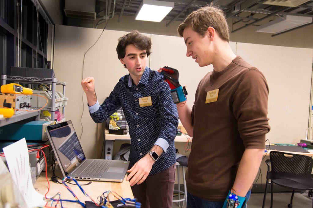 Diapo 2 : Deux personnes testant des prototypes de gants Sign Aloud dans un espace de travail.