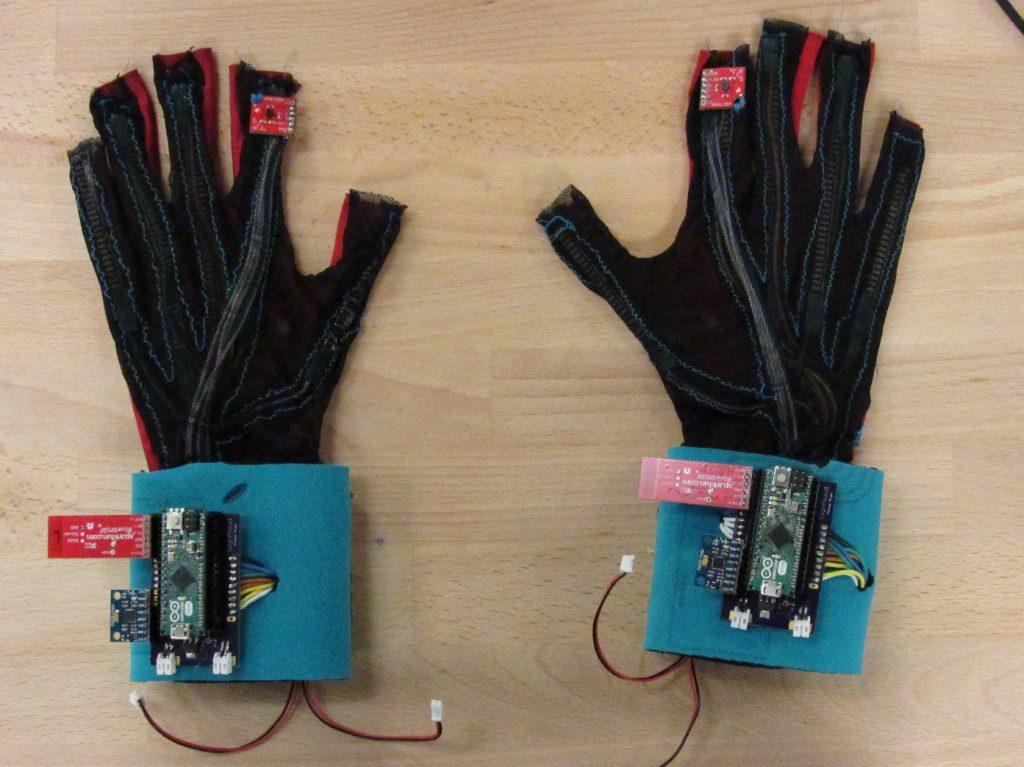 Diapo 3 : Paire de gants Sign Aloud, posée sur une table.