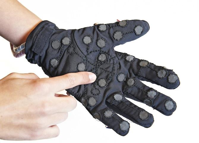 Diapo 4 : Personne appuyant avec sa main droite sur un des capteurs du gant Mobile Lorm Gloves qu'elle porte à sa main gauche.