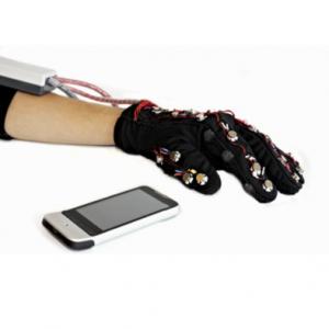 Main portant un prototype de Mobile Lorm Gloves, à coté un smartphone.