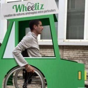 Photo d'un home en fauteuil roulant dans une voiture en carton Wheeliz