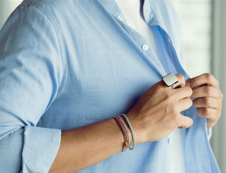 Diapo 7 : Personne portant une bague Orii à la main droite, boutonnant sa chemise.