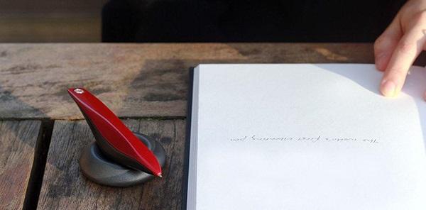 Diapo 1 : Stylo Arc sur son socle, à coté d'un cahier vierge sur une table en bois.