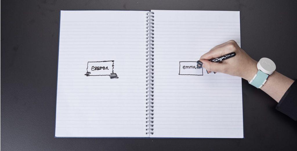 Diapo 3 : Cahier ouvert, page de gauche le mot 'Emma' est écrit de manière peux lisible, à droite une personne équipée d'une montre Emma Watch écrit le mot 'Emma' de manière lisible.