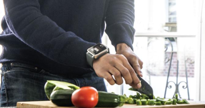 Diapo 6 : Personne portant une montre K'track glucose au poignet droit, découpant des légumes.